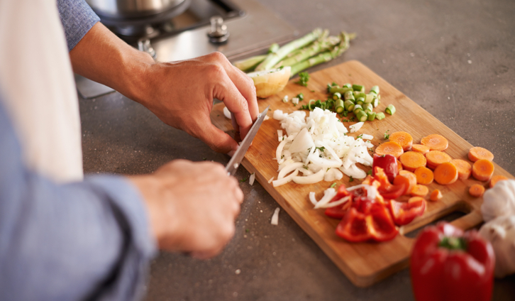 A person cutting vegetables on a cutting board