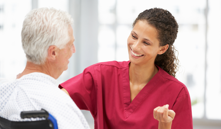 Female nurse smiling at male patient in a wheelchair